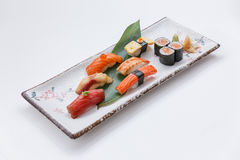 Sushi-Satz umfassen Maguro, Hamachi, Lachse, Kani, Garnele und Tamago Maki mit Salmon Maki Rolls Lizenzfreie Stockfotografie