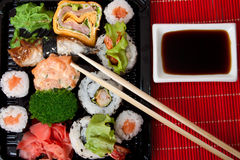 Sushi, sauce and chopstick. On a red bamboo napkin. Series japanese food Royalty Free Stock Photos
