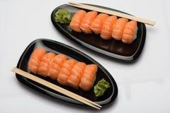 Sushi saumonés, bâtons en bois et wasabi de deux plats en céramique noirs d'une forme en forme de haricot Image stock