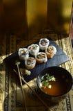Sushi, Schüssel Miso-Suppe, Essstäbchen, Hintergrundbeleuchtungsvorhänge Stockbild