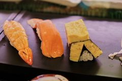 Sushi serve on dish with shrimp egg roll and salmon. Each three stock photos