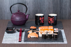 Sushi served on a black ceramic. With teapot and cups Royalty Free Stock Image