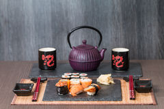Sushi served on a black ceramic. With teapot and cups Stock Photo