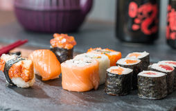 Sushi served on a black ceramic. With teapot and cups Stock Photos