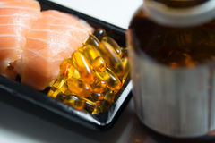 Sushi served with piles of fish oil capsules with brown bottle i Stock Images