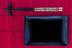 Sushi set with a black plate. And chopsticks on a red bamboo mat Royalty Free Stock Photos