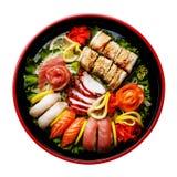 Sushi Set in black Sushioke round plate isolated. Sushi Set nigiri, rolls and sashimi served in traditional Japan black Sushioke round plate isolated Royalty Free Stock Photo