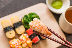Sushi set with chop sticks, wasabi served on wooden slate, selective focus - Sushi is food originating in Japan, consisting of co. Oked vinegar rice combined stock images