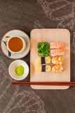 Sushi set with chop sticks, wasabi served on wooden slate, selective focus - Sushi is food originating in Japan, consisting of co. Oked vinegar rice combined royalty free stock photo