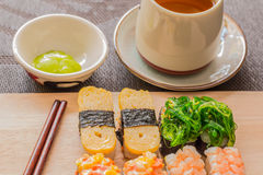 Sushi set with chop sticks, wasabi served on wooden slate, selective focus - Sushi is food originating in Japan, consisting of co. Oked vinegar rice combined stock image
