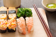Sushi set with chop sticks, wasabi served on wooden slate, selective focus - Sushi is food originating in Japan, consisting of co. Oked vinegar rice combined royalty free stock image