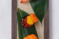 Sushi Set Close-up on Quail Egg Yolk Served on Leaf on Stone Plate. Stock Photos