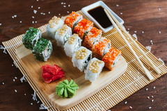 Sushi set on a dark wooden background. Sushi set on a dark wood background with wasabi, ginger and soy sauce Royalty Free Stock Images