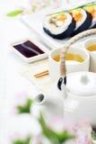 Sushi set, green tea and sakura branch Royalty Free Stock Photos