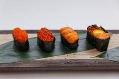 Sushi Set Include Tobiko, Ikura, Sea Urchin and Ikura, Urchin and Quail Egg Yolk Served on Leaf on Stone Plate Stock Photos
