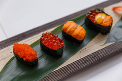 Sushi Set Include Tobiko, Ikura, Sea Urchin and Ikura, Urchin and Quail Egg Yolk Served on Leaf on Stone Plate Stock Photos