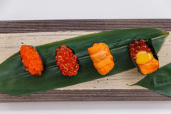Sushi Set Include Tobiko, Ikura, Sea Urchin and Ikura, Urchin and Quail Egg Yolk Served on Leaf on Stone Plate Royalty Free Stock Photos