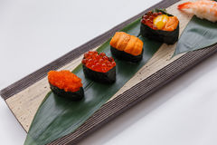 Sushi Set Include Tobiko, Ikura, Sea Urchin and Ikura, Urchin and Quail Egg Yolk Served on Leaf on Stone Plate Royalty Free Stock Image