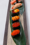 Sushi Set Include Tobiko, Ikura, Sea Urchin and Ikura, Urchin and Quail Egg Yolk Served on Leaf on Stone Plate Royalty Free Stock Images