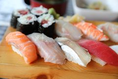 Sushi Set nigiri and sushi maki with tea , Japanese food. Sushi Set nigiri and sushi maki with tea on wooden plate , Japanese food royalty free stock photography