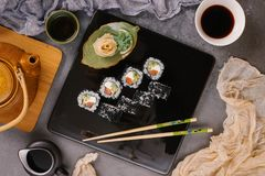 Sushi Set nigiri and sushi rolls in dark ceramic plate with soy sauce, iron teapot and chopsticks over black stone texture stock photo