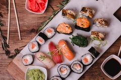 Sushi set nigiri and rolls served on brown wooden table on marbel stone plate. Top view food photography Royalty Free Stock Image