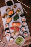 Sushi set nigiri and rolls served on brown wooden table on marbel stone plate. Top view food photography Royalty Free Stock Images