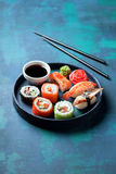 Sushi set nigiri and rolls served in round plate stock images
