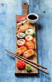Sushi set nigiri and rolls on wooden serving board royalty free stock images