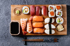 Sushi Set nigiri and rolls. Sushi Set nigiri and sushi rolls on wooden serving board with soy sauce and chopsticks over black stone texture background. Top view royalty free stock photos