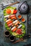 Sushi Set nigiri and sashimi with tea. Served on gray stone slate on metal background stock photos