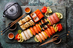 Sushi Set nigiri and sushi rolls with tea. Served on gray stone slate on metal background stock images
