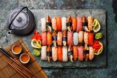 Sushi Set nigiri with tea. Served on gray stone slate on metal background royalty free stock image