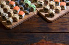 Sushi set of a number of rolls is located on a wooden cutting board on a table in the kitchen of a sushi bar. A traditional dish. Of oriental cuisine Stock Photo