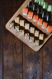 Sushi set of a number of rolls is located on a wooden cutting board on a table in the kitchen of a sushi bar. A traditional dish. Of oriental cuisine royalty free stock images