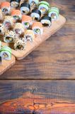 Sushi set of a number of rolls is located on a wooden cutting board on a table in the kitchen of a sushi bar. A traditional dish. Of oriental cuisine stock photography