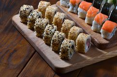 Sushi set of a number of rolls is located on a wooden cutting board on a table in the kitchen of a sushi bar. A traditional dish. Of oriental cuisine Stock Photos