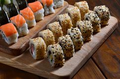 Sushi set of a number of rolls is located on a wooden cutting board on a table in the kitchen of a sushi bar. A traditional dish o. F oriental cuisine stock images