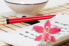 Sushi set and orchid flower on bamboo mat. Sushi set on bamboo  place mat  and red orchids flower on small plate Stock Image