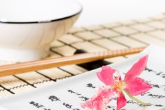 Sushi set and pink orchid flower. Sushi set on bamboo  place mat  and red orchids flower on small plate Royalty Free Stock Photography