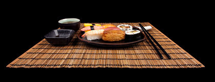 Sushi Set Ready to Go. Place setting with sushi and tea on a bamboo place mat isolated on place Royalty Free Stock Photo