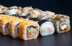 Sushi set rolls with salmon eel cheese cucumber rice sauce sesame caviar. Japanese food mayonnaise masalo scrambled eggs tasty fish traditional black menu stock photo