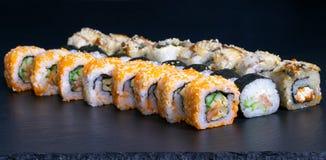 Sushi set rolls with salmon eel cheese cucumber rice sauce sesame caviar. Japanese food mayonnaise masalo scrambled eggs tasty fish traditional black menu royalty free stock photography