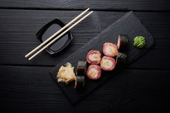 Sushi set with salmon served on black clay plate with soy sauce and chopsticks, top view. Delicious traditional Japanese food with Royalty Free Stock Image