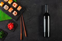 Sushi Set sashimi and sushi rolls, bottle of wine and a glass served on stone slate stock photography