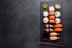 Sushi Set sashimi with salmon, shrimp, eel and sushi rolls philadelphia served on stone slate. Top view with copy space Royalty Free Stock Images