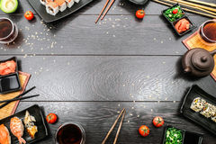 Sushi set sashimi and sushi rolls around dark background. Sushi set sashimi, nigiri, maguro and sushi rolls served on plate with teapot and tomatoes on dark royalty free stock photography