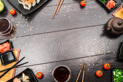 Sushi set sashimi and sushi rolls around dark background. Sushi set sashimi, nigiri, maguro and sushi rolls served on plate with teapot and tomatoes on dark royalty free stock image