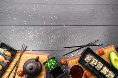 Sushi set sashimi and sushi rolls on dark background. Sushi set sashimi, nigiri, maguro and sushi rolls served on plate with teapot and tomatoes on dark wooden Stock Photo