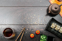 Sushi set sashimi and sushi rolls on dark background. Sushi set sashimi served on plate with teapot and tomatoes on dark wooden background. Space for text Stock Images